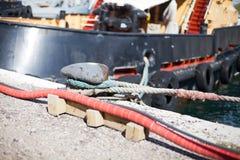 Το σκάφος δένεται σε μια αλυσίδα σχοινιών σκαλών αποβαθρών στοκ φωτογραφίες