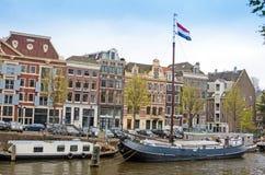 Το σκάφος με την ολλανδική σημαία στο κανάλι στο Άμστερνταμ, Κάτω Χώρες, Στοκ φωτογραφία με δικαίωμα ελεύθερης χρήσης