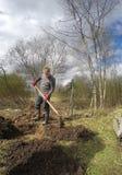 Το σκάψιμο νεαρών άνδρων άλεσαν και να προετοιμαστούν για τη φύτευση στο υγρό χώμα την πρώιμη άνοιξη Στοκ Εικόνες