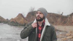 Το σκεπτικό άτομο περπατά κατά μήκος της θάλασσας Κοιτάζει προς τα εμπρός και κεκλεισμένων των θυρών, κρύος καιρός πτώσης φιλμ μικρού μήκους