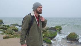 Το σκεπτικό άτομο περπατά κατά μήκος της θάλασσας Κοιτάζει προς τα εμπρός και κεκλεισμένων των θυρών, κρύος καιρός πτώσης απόθεμα βίντεο