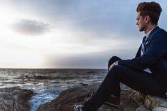 Το σκεπτικό άτομο στο κοστούμι κάθεται στους βράχους κοντά στη θάλασσα και τη σκέψη Νέος τύπος στοκ φωτογραφίες