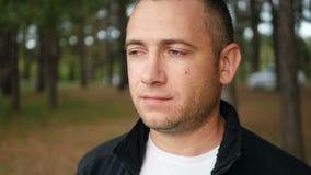 Το σκεπτικό βάναυσο άτομο με τις καλαμιές στο πρόσωπό του εξετάζει την απόσταση υπαίθρια Αρσενικός τουρίστας στο δάσος απόθεμα βίντεο