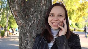 Το σκεπτικό κορίτσι με το smartphone παραδίδει μέσα το πάρκο πόλεων η γυναίκα εξετάζει την οθόνη του κινητού τηλεφώνου στο κλίμα  απόθεμα βίντεο