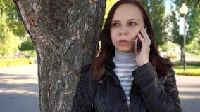 Το σκεπτικό κορίτσι με το smartphone παραδίδει μέσα το πάρκο πόλεων η γυναίκα εξετάζει την οθόνη του κινητού τηλεφώνου στο κλίμα  φιλμ μικρού μήκους