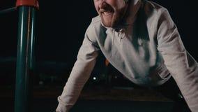 Το σκληραγωγημένο άτομο κάνει pushup στην περιοχή πάρκων της πόλης στη νύχτα, άποψη του προσώπου απόθεμα βίντεο