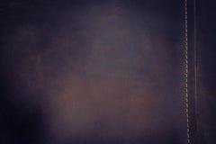 Το σκοτεινές καφετιές υπόβαθρο και η σύσταση δέρματος Nubuck με το χρυσό s Στοκ Φωτογραφία