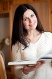 Το σκοτεινός-μαλλιαρό κορίτσι διαβάζει το βιβλίο Στοκ εικόνες με δικαίωμα ελεύθερης χρήσης
