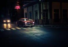 Το σκούρο κόκκινο oldtimer περνά τα σταυροδρόμια τη νύχτα κάτω από streetlamp Στοκ εικόνα με δικαίωμα ελεύθερης χρήσης
