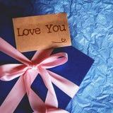 Το σκούρο μπλε κιβώτιο δώρων με τη διακόσμηση κορδελλών και σας αγαπά αυτοκίνητο κειμένων Στοκ Εικόνες