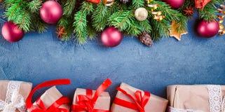 Το σκούρο μπλε υπόβαθρο Χριστουγέννων με το έλατο διακλαδίζεται και νέο ντεκόρ έτους, παιχνίδια και κιβώτια δώρων σε μια πλάκα ή  Στοκ φωτογραφία με δικαίωμα ελεύθερης χρήσης