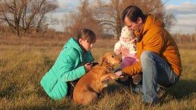 Το σκυλί γλείφει τη μύτη ιδιοκτητών ` s, η οποία περπατά με τα παιδιά του φιλμ μικρού μήκους