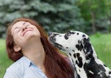 Το σκυλί πρόκειται να φιλήσει τον ιδιοκτήτη του -- νέα γυναίκα στοκ φωτογραφία με δικαίωμα ελεύθερης χρήσης