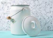 Το σμαλτωμένο γάλα μπορεί με το καπάκι στο άσπρο υπόβαθρο συμπαγών τοίχων στοκ φωτογραφίες