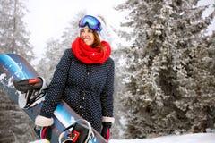 Το σνόουμπορντ λαβής κοριτσιών και πηγαίνει να κάνει σκι Στοκ εικόνα με δικαίωμα ελεύθερης χρήσης