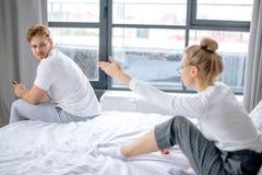 Το σοβαρό άτομο ξανακοιτάζει ενώ η σύζυγός του τον επιπλήττει για την τεμπελιά στοκ φωτογραφίες