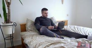Το σοβαρό άτομο στα γυαλιά δακτυλογραφεί στο lap-top στο σπίτι στην κρεβατοκάμαρα φιλμ μικρού μήκους