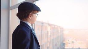 Το σοβαρό καυκάσιο επιχειρησιακό παιδί φαίνεται παράθυρο γραφείων φιλμ μικρού μήκους