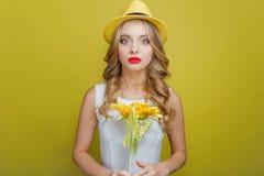 Το σοβαρό κορίτσι κρατά την όμορφη ανθοδέσμη με τα λουλούδια ήλιων Κοιτάζει στη κάμερα Απομονωμένος στην κίτρινη ανασκόπηση Στοκ Εικόνα
