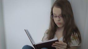 Το σοβαρό μικρό κορίτσι στα γυαλιά κάνει επιμελώς την εργασία του στο παράθυρο απόθεμα βίντεο