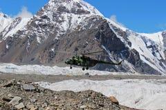 Το σοβιετικό ελικόπτερο με τους ορειβάτες που προσγειώνονται σε Khan Tengri και η μέγιστη βάση Pobeda στρατοπεδεύουν (Κιργιστάν) Στοκ Φωτογραφία
