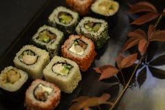 Το σούσι και το σούσι κυλούν, nigiri σουσιών στο πιάτο πετρών στο σκοτεινό υπόβαθρο Στοκ Εικόνες