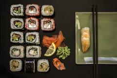 Το σούσι και το σούσι κυλούν, nigiri σουσιών στο πιάτο πετρών στο σκοτεινό υπόβαθρο Στοκ Εικόνα