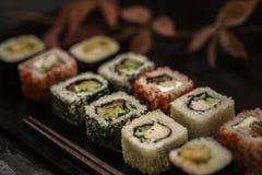 Το σούσι και το σούσι κυλούν, nigiri σουσιών στο πιάτο πετρών στο σκοτεινό υπόβαθρο Στοκ Φωτογραφίες