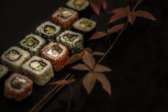 Το σούσι και το σούσι κυλούν, nigiri σουσιών στο πιάτο πετρών στο σκοτεινό υπόβαθρο Στοκ φωτογραφία με δικαίωμα ελεύθερης χρήσης