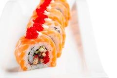Το σούσι κυλά με το σολομό, το χέλι, το αγγούρι και το tobiko στο άσπρο πιάτο Στοκ εικόνες με δικαίωμα ελεύθερης χρήσης