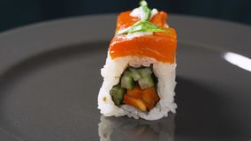Το σούσι κυλά τα ιαπωνικά τρόφιμα που περιστρέφονται πέρα από το μαύρο υπόβαθρο Ρόλος σουσιών με τον τόνο, λαχανικά, tofu κινηματ απόθεμα βίντεο