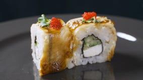 Το σούσι κυλά τα ιαπωνικά τρόφιμα που περιστρέφονται πέρα από το μαύρο υπόβαθρο Ρόλος σουσιών με το χέλι, το χαβιάρι, και την κιν απόθεμα βίντεο