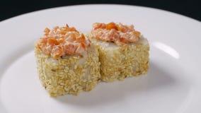 Το σούσι κυλά τα ιαπωνικά τρόφιμα που περιστρέφονται πέρα από το μαύρο υπόβαθρο Ρόλος σουσιών με το σολομό, tofu, τα λαχανικά και απόθεμα βίντεο
