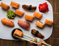 Το σούσι κυλά τα χέρια γυναικών πιπεροριζών και wasabi Στοκ Εικόνες