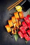 Το σούσι κυλά την κινηματογράφηση σε πρώτο πλάνο Ιαπωνικά τρόφιμα στο εστιατόριο Ρόλος με το σολομό, το χέλι, τα λαχανικά και το  Στοκ εικόνα με δικαίωμα ελεύθερης χρήσης