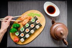 Το σούσι κυλά, σάλτσας και γυναικών chopsticks εκμετάλλευσης χεριών σε ένα γκρίζο υπόβαθρο Τοπ όψη Επίπεδος βάλτε Στοκ Εικόνες