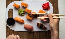 Το σούσι κυλά τα χέρια γυναικών πιπεροριζών και wasabi Στοκ εικόνες με δικαίωμα ελεύθερης χρήσης