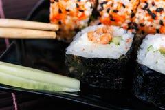 Το σούσι κυλά την κατάταξη στο μαύρα πιάτο και chopsticks Στοκ Εικόνα
