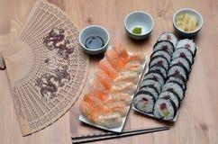 Το σούσι της Maki κυλούν και το σούσι nigiri με τα τρόφιμα σολομών και της Ιαπωνίας γαρίδων στον πίνακα με τη σάλτσα και την πιπε Στοκ Εικόνα