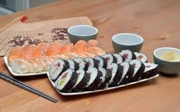 Το σούσι της Maki κυλούν και το σούσι nigiri στα τρόφιμα της Ιαπωνίας πιάτων στην επιτραπέζια λεπτομέρεια Στοκ Εικόνα