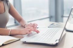 Το σπίτι-γραφείο μιας απόστασης υιοθέτησε θηλυκό freelancer, κείμενο δακτυλογράφησης, χρησιμοποιώντας τη ηλεκτρονική συσκευή της στοκ εικόνες με δικαίωμα ελεύθερης χρήσης