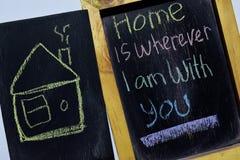 Το σπίτι είναι οπουδήποτε είμαι με σας ζωηρόχρωμο σε χειρόγραφο φράσης στον πίνακα στοκ φωτογραφίες