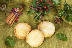 Το σπίτι που ψήνεται κομματιάζει τις πίτες για τα Χριστούγεννα με τα φύλλα ελαιόπρινου Στοκ Φωτογραφίες