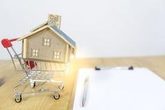 Το σπίτι στη σύμβαση κάρρων αγορών του σπιτιού αγορών, πώς να γίνει ένας ιδιοκτήτης σπιτιού, έννοιες για on-line να ψωνίσει, αγορ στοκ φωτογραφία