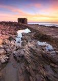 Το σπίτι φρουρών σε μια απομονωμένη ακτή σχετικά με το ηλιοβασίλεμα Στοκ φωτογραφίες με δικαίωμα ελεύθερης χρήσης