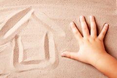 Το σπίτι χρωματίζεται στην άμμο από το χέρι του παιδιού Σπίτι έννοιας θαλασσίως Στοκ φωτογραφία με δικαίωμα ελεύθερης χρήσης