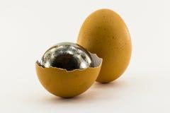 Το σπασμένο αυγό με μια σφαίρα χάλυβα μέσα στο κοχύλι και ολόκληρο ένα αυγό είναι Στοκ εικόνες με δικαίωμα ελεύθερης χρήσης