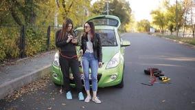 Το σπασμένο αυτοκίνητο δύο γυναικών πλησίον στο δρόμο καλεί το κινητό τηλέφωνο Το πρόβλημα στο δρόμο Η διακοπή ενός αυτοκινήτου απόθεμα βίντεο