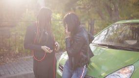 Το σπασμένο αυτοκίνητο δύο γυναικών πλησίον στο δρόμο καλεί το κινητό τηλέφωνο Το πρόβλημα στο δρόμο Η διακοπή ενός αυτοκινήτου φιλμ μικρού μήκους