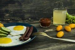 Το σπιτικό εύγευστο πρόγευμα με την ηλιόλουστη πλευρά τηγάνισε επάνω το αυγό, λουκάνικο, ντομάτες κατά τη τοπ άποψη στοκ εικόνες